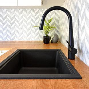 Bild på en liten funkis bruna l-formad brunt tvättstuga enbart för tvätt, med en undermonterad diskho, luckor med glaspanel, vita skåp, träbänkskiva, grå väggar, klinkergolv i keramik, en tvättmaskin och torktumlare bredvid varandra och grått golv