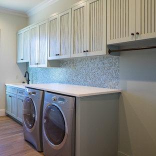 Idee per una lavanderia mediterranea con lavello a vasca singola, ante a filo, ante grigie, top in quarzite, pareti beige, pavimento in legno massello medio, lavatrice e asciugatrice affiancate e pavimento beige