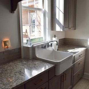 Foto di una piccola sala lavanderia tradizionale con lavello stile country, ante in stile shaker, ante in legno scuro, top in granito, pareti bianche, pavimento in gres porcellanato, pavimento marrone e top grigio