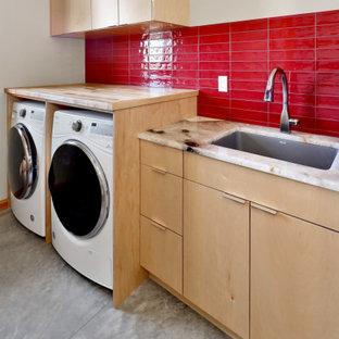 Foto på en mellanstor rustik flerfärgade u-formad tvättstuga enbart för tvätt, med en undermonterad diskho, släta luckor, skåp i ljust trä, bänkskiva i kvarts, rött stänkskydd, stänkskydd i keramik, vita väggar, betonggolv, en tvättmaskin och torktumlare bredvid varandra och grått golv