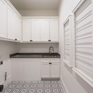 Inspiration for a contemporary gray floor laundry room remodel in Houston with a farmhouse sink, gray cabinets, white backsplash, ceramic backsplash, gray countertops, onyx countertops, white walls and a side-by-side washer/dryer