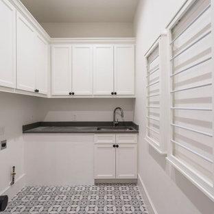 Modern inredning av en grå grått tvättstuga, med en rustik diskho, grå skåp, vitt stänkskydd, stänkskydd i keramik, bänkskiva i onyx, vita väggar, en tvättmaskin och torktumlare bredvid varandra och grått golv