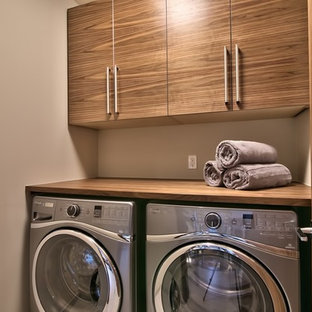 Inspiration for a small contemporary single-wall laundry closet remodel in Other with flat-panel cabinets, medium tone wood cabinets, wood countertops, beige walls and brown countertops