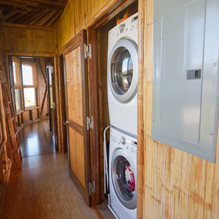 Tropical laundry cupboard in Hawaii with cork floors and a stacked washer and dryer.