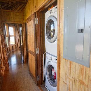 Ispirazione per un ripostiglio-lavanderia tropicale con pavimento in sughero e lavatrice e asciugatrice a colonna