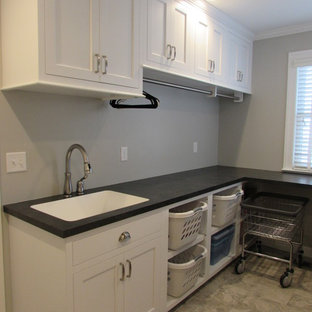 Medium sized classic single-wall separated utility room in DC Metro with a submerged sink, recessed-panel cabinets, white cabinets, composite countertops, white walls, ceramic flooring, a side by side washer and dryer and black worktops.