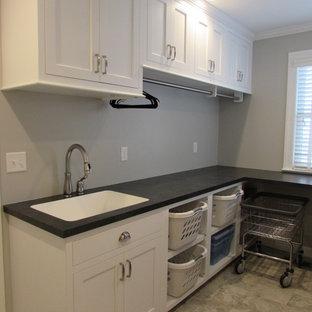 Idéer för mellanstora vintage linjära svart tvättstugor enbart för tvätt, med en undermonterad diskho, luckor med infälld panel, vita skåp, bänkskiva i koppar, vita väggar, klinkergolv i keramik och en tvättmaskin och torktumlare bredvid varandra