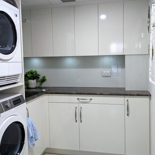 Photo of a small contemporary l-shaped dedicated laundry room in Brisbane with a drop-in sink, flat-panel cabinets, grey cabinets, granite benchtops, grey splashback, glass sheet splashback, white walls, a stacked washer and dryer and black benchtop.