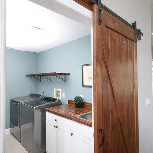 Пример оригинального дизайна: маленькая линейная универсальная комната в стиле кантри с накладной раковиной, фасадами в стиле шейкер, белыми фасадами, деревянной столешницей, синими стенами, полом из керамогранита и со стиральной и сушильной машиной рядом