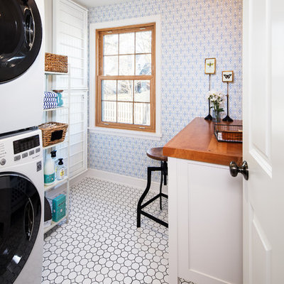 Example of a classic single-wall white floor dedicated laundry room design in Omaha with white cabinets, wood countertops, blue walls, a stacked washer/dryer and brown countertops
