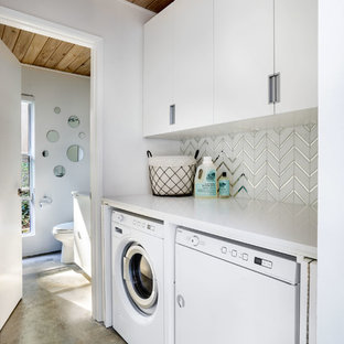 Idee per una piccola sala lavanderia minimalista con ante lisce, ante bianche, top in quarzo composito, pareti bianche, pavimento in cemento, lavatrice e asciugatrice nascoste, pavimento grigio e top bianco