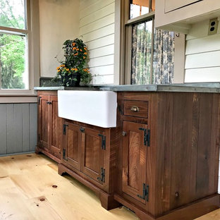 Design ideas for a mid-sized country utility room in Philadelphia with a farmhouse sink, shaker cabinets, dark wood cabinets, zinc benchtops, beige walls, light hardwood floors, brown floor and grey benchtop.