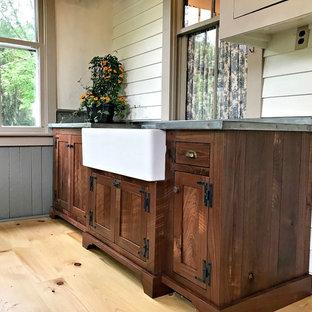 Cette image montre une buanderie rustique multi-usage et de taille moyenne avec un évier de ferme, un placard à porte shaker, des portes de placard en bois sombre, un plan de travail en zinc, un mur beige, un sol en bois clair, un sol marron et un plan de travail gris.