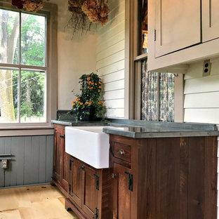 Inredning av ett lantligt mellanstort grå grått grovkök, med en rustik diskho, skåp i shakerstil, skåp i mörkt trä, bänkskiva i zink, beige väggar, ljust trägolv och brunt golv