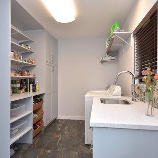 Foto på ett mellanstort funkis parallellt grovkök, med en undermonterad diskho, luckor med infälld panel, grå skåp, bänkskiva i kvartsit, grå väggar, skiffergolv och en tvättmaskin och torktumlare bredvid varandra