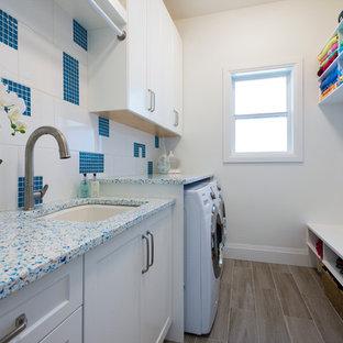 Idéer för att renovera ett mellanstort vintage parallellt grovkök, med en undermonterad diskho, skåp i shakerstil, vita skåp, bänkskiva i återvunnet glas, grå väggar, klinkergolv i porslin och en tvättmaskin och torktumlare bredvid varandra