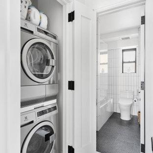 Klassisk inredning av en liten tvättstuga, med vita väggar, klinkergolv i porslin, en tvättpelare och svart golv