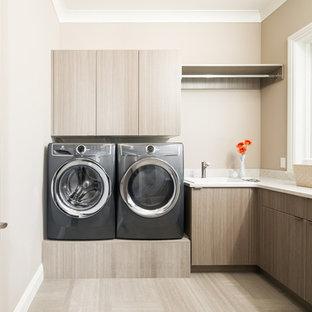 Klassisk inredning av en vita vitt tvättstuga enbart för tvätt, med släta luckor, beige väggar, en tvättmaskin och torktumlare bredvid varandra, beiget golv och grå skåp