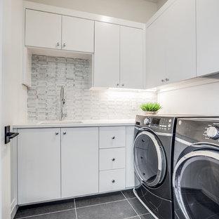 Idee per una sala lavanderia mediterranea di medie dimensioni con lavello da incasso, ante lisce, ante bianche, top in quarzite, pareti bianche, pavimento in gres porcellanato, lavatrice e asciugatrice affiancate, pavimento grigio e top bianco