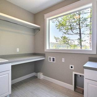 Ispirazione per una grande lavanderia multiuso design con lavello da incasso, ante con bugna sagomata, ante bianche, top piastrellato, pareti beige, pavimento in gres porcellanato, lavatrice e asciugatrice affiancate e pavimento grigio