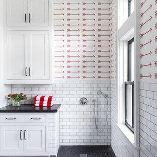 Exempel på ett stort lantligt grå u-format grått grovkök, med en undermonterad diskho, luckor med infälld panel, vita skåp, bänkskiva i betong, röda väggar, kalkstensgolv, en tvättmaskin och torktumlare bredvid varandra och svart golv