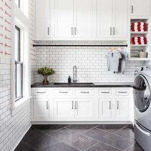 Inredning av ett lantligt stort grå u-format grått grovkök, med en undermonterad diskho, luckor med infälld panel, vita skåp, bänkskiva i betong, röda väggar, kalkstensgolv, en tvättmaskin och torktumlare bredvid varandra och svart golv