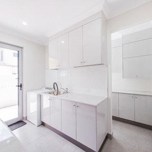 Idéer för ett stort modernt vit parallellt grovkök, med en enkel diskho, släta luckor, vita skåp, laminatbänkskiva, vita väggar, en tvättpelare, vitt stänkskydd, glaspanel som stänkskydd, klinkergolv i keramik och grått golv