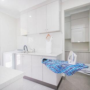 Inredning av ett modernt stort vit parallellt vitt grovkök, med en enkel diskho, släta luckor, vita skåp, laminatbänkskiva, vita väggar, vitt stänkskydd, glaspanel som stänkskydd, klinkergolv i keramik, en tvättpelare och grått golv
