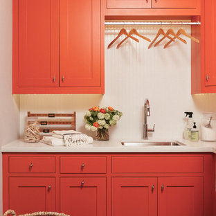 Photo of a mid-sized country l-shaped utility room in San Francisco with an undermount sink, quartz benchtops, white walls, slate floors, a side-by-side washer and dryer, shaker cabinets and red cabinets.