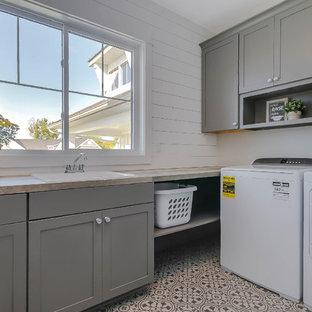 Ispirazione per una sala lavanderia country di medie dimensioni con lavello da incasso, ante in stile shaker, ante grigie, top in laminato, pareti bianche, pavimento in vinile, lavatrice e asciugatrice affiancate, pavimento grigio e top marrone