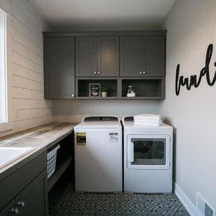 Inredning av en lantlig mellanstor bruna l-formad brunt tvättstuga enbart för tvätt, med en nedsänkt diskho, skåp i shakerstil, grå skåp, laminatbänkskiva, grå väggar, linoleumgolv, en tvättmaskin och torktumlare bredvid varandra och grått golv