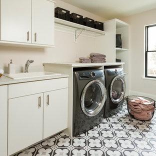Immagine di una grande sala lavanderia chic con lavello da incasso, ante lisce, ante bianche, top in laminato, pareti rosa, lavatrice e asciugatrice affiancate, pavimento multicolore, pavimento in cemento e top bianco
