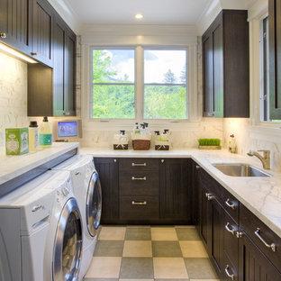 Idéer för att renovera en vintage u-formad tvättstuga enbart för tvätt, med skåp i mörkt trä, en tvättmaskin och torktumlare bredvid varandra och flerfärgat golv