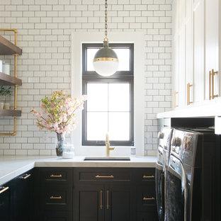 Inredning av en klassisk vita u-formad vitt tvättstuga enbart för tvätt, med en undermonterad diskho, skåp i shakerstil, svarta skåp, vita väggar och en tvättmaskin och torktumlare bredvid varandra