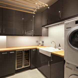 Photo of a small modern u-shaped utility room with a farmhouse sink, flat-panel cabinets, grey cabinets, wood benchtops, grey splashback, glass sheet splashback, an integrated washer and dryer and beige benchtop.