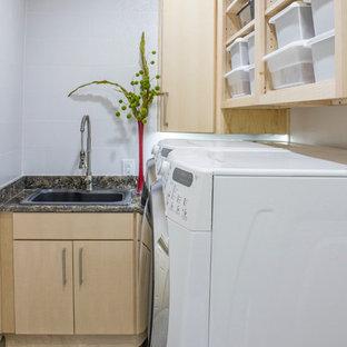 Idéer för en liten modern l-formad tvättstuga enbart för tvätt, med släta luckor, skåp i ljust trä, granitbänkskiva, vita väggar, klinkergolv i porslin, en tvättmaskin och torktumlare bredvid varandra och en nedsänkt diskho