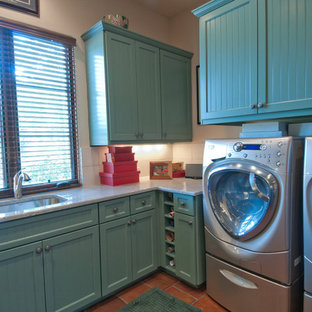 This is an example of a mid-sized country l-shaped utility room in Austin with an undermount sink, granite benchtops, a side-by-side washer and dryer and blue cabinets.