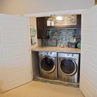 Cette image montre une petit buanderie linéaire traditionnelle avec un placard, un placard à porte shaker, des portes de placard en bois sombre, un plan de travail en granite, un sol en carrelage de porcelaine, des machines côte à côte et un mur gris.