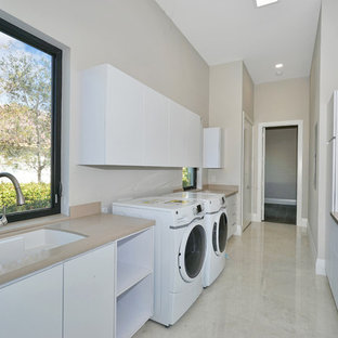 Example of a large minimalist galley marble floor and beige floor dedicated laundry room design in Miami with an undermount sink, flat-panel cabinets, white cabinets, marble countertops and beige walls
