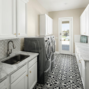 Example of a mid-sized transitional galley ceramic floor and black floor dedicated laundry room design in Phoenix with an undermount sink, white cabinets, quartz countertops, beige walls, gray countertops and recessed-panel cabinets