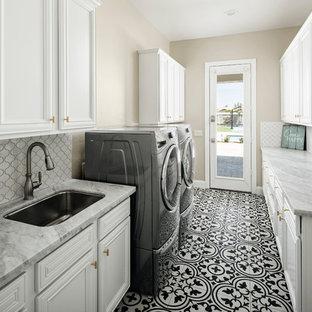 Idee per una sala lavanderia classica di medie dimensioni con lavello sottopiano, ante bianche, top in quarzo composito, pareti beige, pavimento con piastrelle in ceramica, lavatrice e asciugatrice affiancate, pavimento nero, top grigio e ante con riquadro incassato