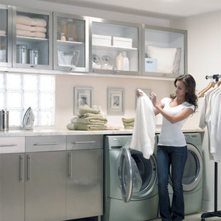 Example of a large trendy dedicated laundry room design in Minneapolis with glass-front cabinets, gray cabinets and beige walls
