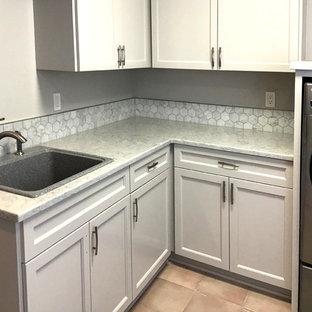 Inspiration för en mellanstor lantlig vita l-formad vitt tvättstuga enbart för tvätt, med en enkel diskho, luckor med profilerade fronter, grå skåp, granitbänkskiva, grå väggar, klinkergolv i keramik, en tvättmaskin och torktumlare bredvid varandra och rosa golv
