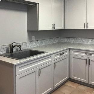 Foto på en mellanstor lantlig vita l-formad tvättstuga enbart för tvätt, med en enkel diskho, luckor med profilerade fronter, grå skåp, granitbänkskiva, grå väggar, klinkergolv i keramik, en tvättmaskin och torktumlare bredvid varandra och rosa golv