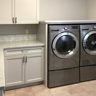 Immagine di una sala lavanderia country di medie dimensioni con lavello a vasca singola, ante a filo, ante grigie, top in granito, pareti grigie, pavimento con piastrelle in ceramica, lavatrice e asciugatrice affiancate, pavimento rosa e top bianco