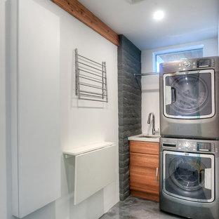 Exempel på en mellanstor modern tvättstuga, med vita väggar, betonggolv, en tvättpelare, släta luckor, skåp i mellenmörkt trä, bänkskiva i kvartsit och en undermonterad diskho