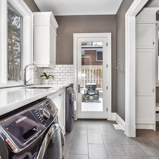 Bild på en stor vintage vita linjär vitt tvättstuga enbart för tvätt, med en undermonterad diskho, luckor med profilerade fronter, vita skåp, bänkskiva i kvarts, klinkergolv i porslin, en tvättmaskin och torktumlare bredvid varandra, grått golv och grå väggar