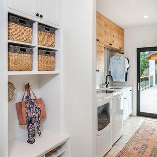 Idéer för att renovera ett lantligt vit vitt grovkök, med en undermonterad diskho, vita väggar, en tvättmaskin och torktumlare bredvid varandra, skåp i shakerstil, vita skåp och brunt golv