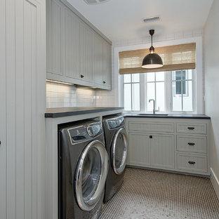 Esempio di una sala lavanderia country di medie dimensioni con lavello sottopiano, ante con riquadro incassato, ante grigie, top in saponaria, pareti grigie, lavatrice e asciugatrice affiancate e top nero