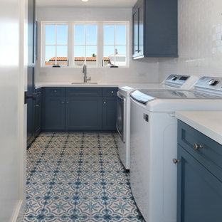 This is an example of a large coastal u-shaped separated utility room in Orange County with a submerged sink, shaker cabinets, blue cabinets, composite countertops, ceramic flooring, a side by side washer and dryer, multi-coloured floors and white worktops.
